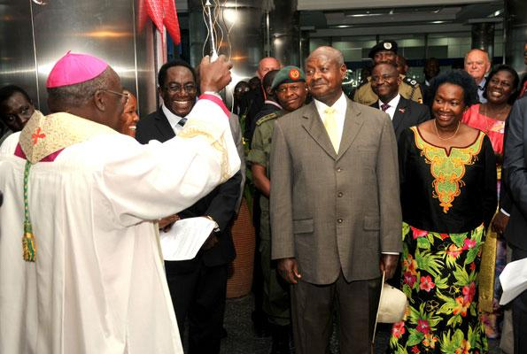 Archbishop John Baptist Odama sprinkles holy water on President Museveni  as Centenary Bank chairman John Ddumba Sentamu (2nd L) and Finance Minister Maria Kiwanuka (R) look on during the opening of the bank's new headquarters in Kampala yesterday.