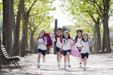 niños con mochilas corriendo en un parque