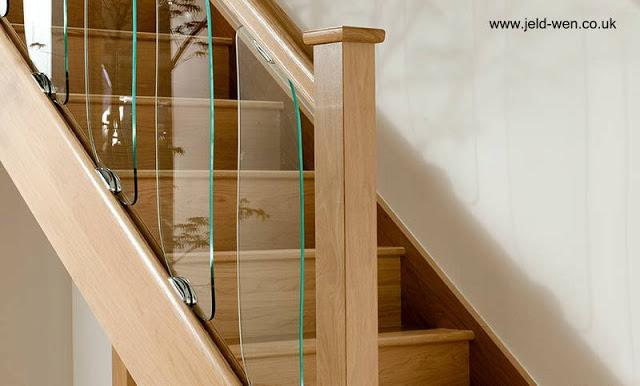 Escalera de madera para interior con vidrios en la barandilla