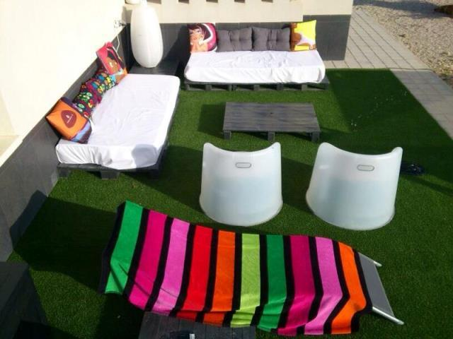 Rinc n chill out con palets cojines y cesped artificial - Como hacer cojines para palets ...