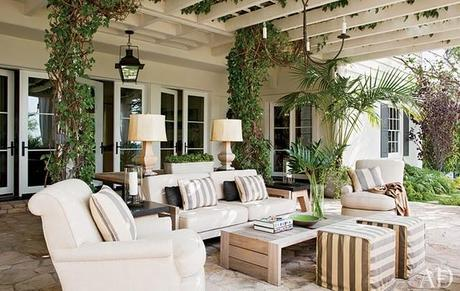 Beautiful covered deck patio with stone floors, iron lanterns, white sofas & chairs, wood cocktail table, white & gray striped cube ottomans, white & gray striped pillows, wood lamps and French doors.