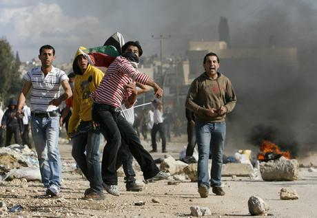 Palestinian youths throw stones during protest in Baqa Ash-Sharqiya
