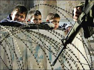 Niños en la valla de Gaza y al otro lado un militar israelí en el 2009. / AlphaBetaUnlimited
