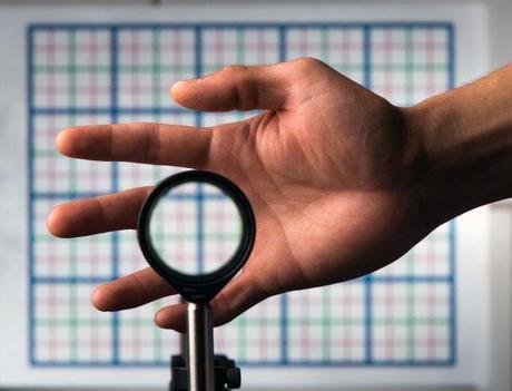 La parte de una mano vista a través de una lente se hace completamente invisible. © Universidad de Rochester