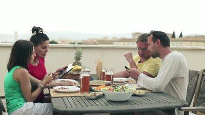 Imagen de http://ak3.picdn.net/shutterstock/videos/2379755/preview/stock-footage-four-friends-with-tablet-and-smartphone-by-the-table-full-of-food.jpg