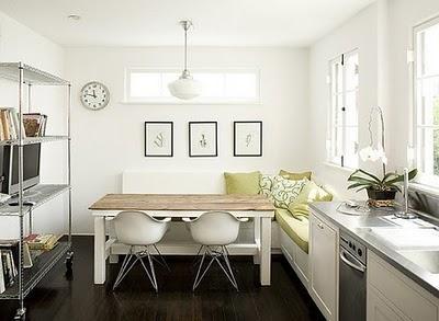 Cocina blanca con banco en esquina y sillas eames