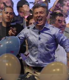 Macri festeja su triunfo, escoltado por el senador Alfredo de Angeli y el diputado Sergio Bergman.