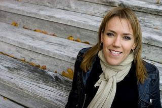 Escritora sueca Asa Larsson, mujer rubia de piel blanca, con chaqueta tipo cuero y bufanda beig.