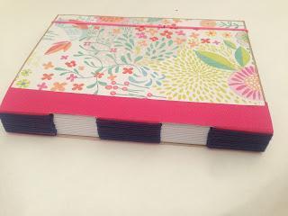 Cuaderno rosa con encuadernación de ojal.