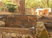 Rocalla bancos piedra traviesas madera jardín secreto.