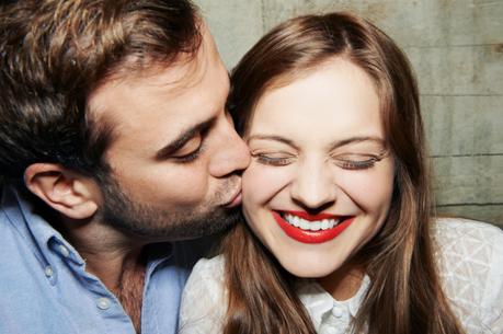 Hombre joven besando en la mejilla a una mujer jóven, con los labios pintados de rojo y sonriendo con los ojos cerrados.
