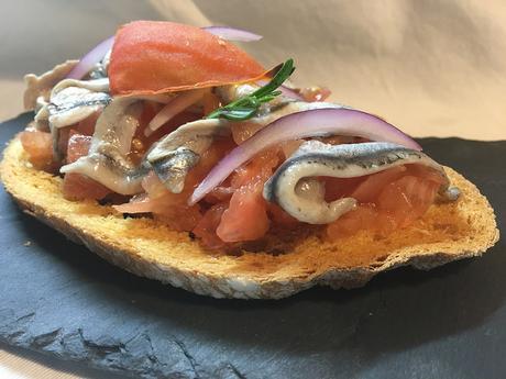 Tostas de pan payes con tomate escaldado y boquerones con sal maldón