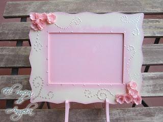 Decorar un marco de madera con flores de papel hechas por ti misma.