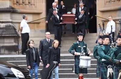 Gaiteros despiden a Malcolm Young en su funeral mientras Angus introduce su guitarra en el coche fúnebre
