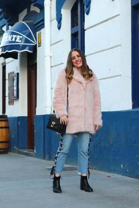 Con abrigo rosa y jeans entre lazados