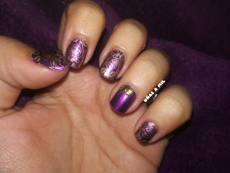 Diseño de uñas en morado y dorado con tachuelas