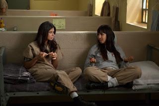 Flaca y marizza, de la serie Orange is the New Black, hablando y sentadas en una carcel.