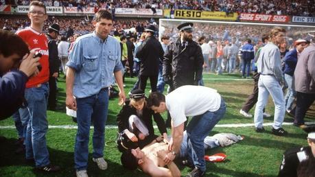 Los rescatistas ayudan a los fanáticos del fútbol en el estadio Hillsborough, en Sheffield, el 15 de abril de 1989, cuando 96simpatizantesdel Liverpool Football Club murieron aplastados y cientos resultaron heridos luego de que se derrumbaran las barandillas de apoyo durante una semifinal de la FA Cup entre Liverpool y Nottingham Forest
