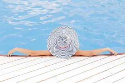 Mujer en la piscina con una pamela