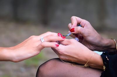 Mujer aplicando a otra una capa de top coat sobre el esmalte de uñas