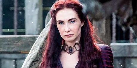 Fotograma de Juego de Tronos, en la que se ve a la hechicera Melisandre, con el pelo y el vestido rojos, piel pálida y su collar protector al cuello.
