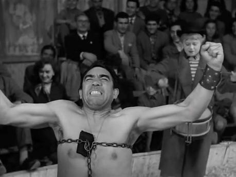 Zampanó (Anthony Quinn) en su acto de la cadena. Atrás Gelsomina (Giulietta Masina) asistiéndolo con el tambor.