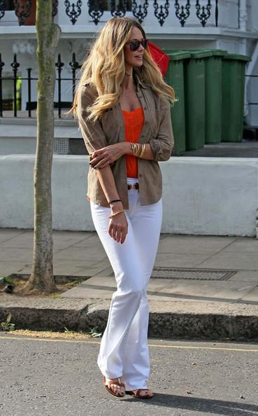Elle MacPherson ****NO GERMANY / SWITZERLAND****.Elle Macpherson looks good in white trousers and bright orange top.