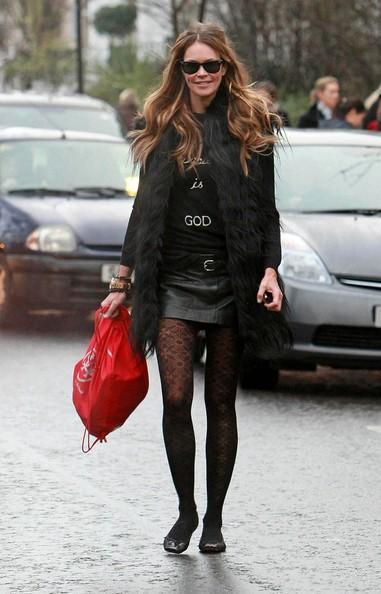 Elle MacPherson Elle Macpherson is looking good in a leather miniskirt and fishnet flowery tights on the school run.