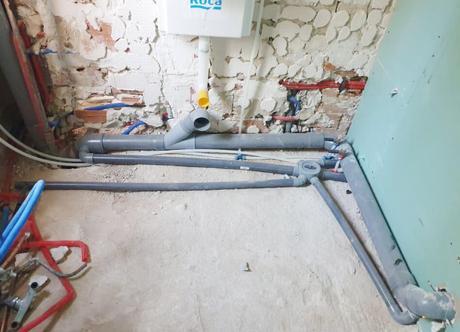 Instalación para dos baños contiguos, de derecha a izquierda: manguetón inodoro 2, bote sifónico (lo que parece un pulpo) manguetón inodoro 1 y bajante. Aquí lo solucionamos con una mocheta para el manguetón 2 que queda por debajo del lavabo del baño 1