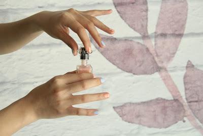 Mujer abriendo una botellita de esmalte de uñas con un fondo de flores de acuarela detrás