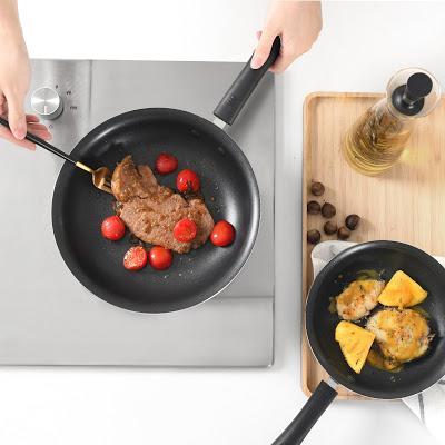 Sartenes antiadherentes con una persona retirando un filete con un tenedor