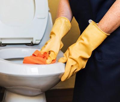 Persona limpiando un inodoro con guantes