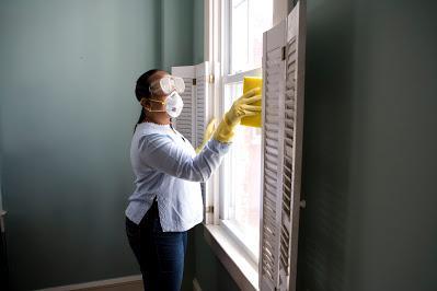 Mujer limpiando una ventana con mascarilla y gafas