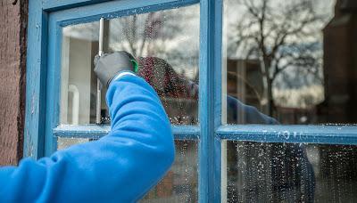 Persona limpiando las ventanas con agua y detergente
