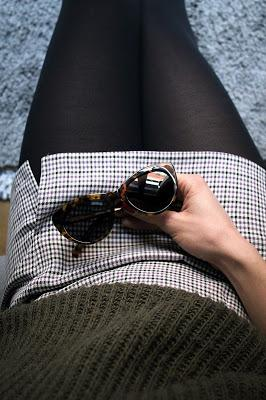 Mujer con medias y minifalda, sosteniendo unas gafas de sol en el regazo