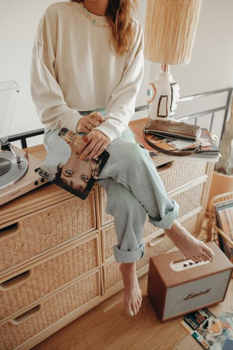 Must-loved denim wearing Agolde jeans and cropped sweatshirt at home