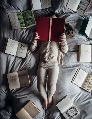 Mujer rodeada de libros abiertos leyendo en la cama