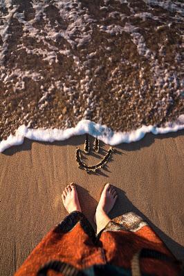 Mujer descalza a la orilla del mar