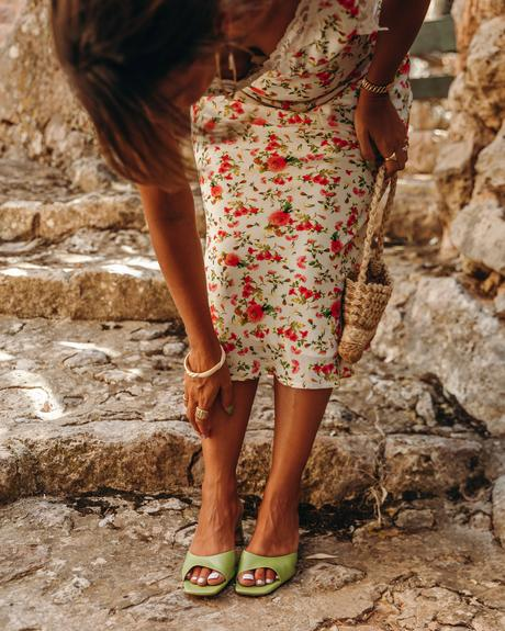 Sara from Collage Vintage wearing a summer midi floral dress, green mules and a mini basket