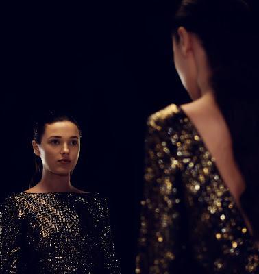 Mujer mirándose en el espejo del probador con un vestido de lentejuelas