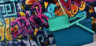 Cubo de fregona delante de una pared con graffities