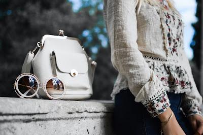 Mujer posando junto a un bolso y unas gafas de sol