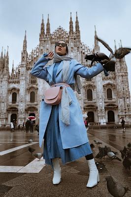 Mujer posando con un look en azules, grises y blancos