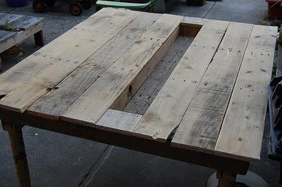 Una mesa de comedor con palets, decorada con suculentas