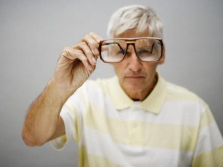Portrait of smiling senior man holding glasses, studio shot